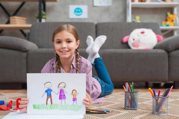 Souriant fille allongée sur un tapis montrant le dessin de sa famille dessiné sur du papier blanc Photo gratuit