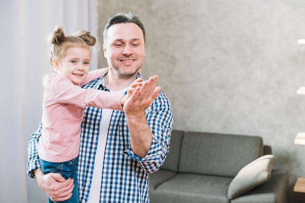 Souriant fille applaudissant sur la main de son père dans le salon Photo gratuit