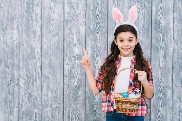 Souriant fille tenant des oeufs de pâques dans le panier, pointant le doigt à la recherche d'appareil photo Photo gratuit