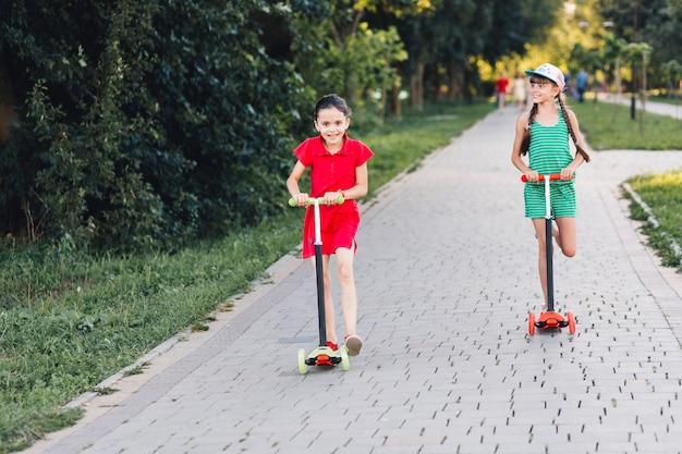 Souriant filles à cheval sur push scooter sur passerelle dans le parc Photo gratuit