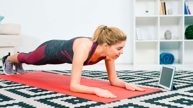 Souriant fit femme faisant la planche en regardant tablette numérique sur tapis rouge à la maison dans le salon Photo gratuit
