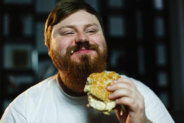 Souriant gros homme mange burger assis devant un téléviseur Photo gratuit