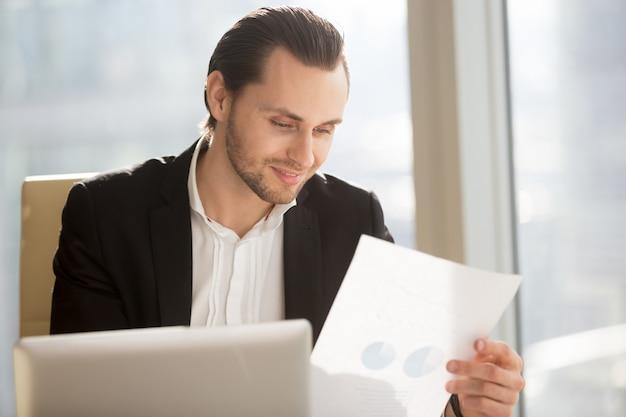 Souriant homme d'affaires en regardant le rapport financier Photo gratuit