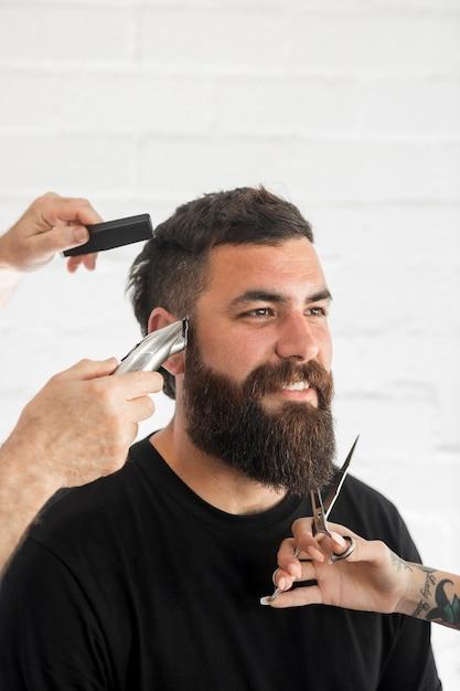 Souriant homme barbu en salon de coiffure Photo gratuit