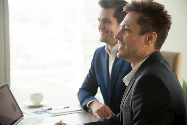 Souriant hommes d'affaires attentifs assistant à une réunion de conférence, côté Photo gratuit
