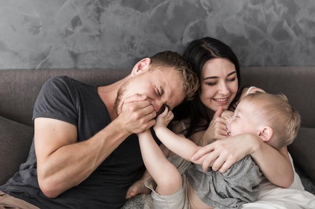 Souriant jeune couple assis sur un canapé en jouant avec leur petit fils Photo gratuit