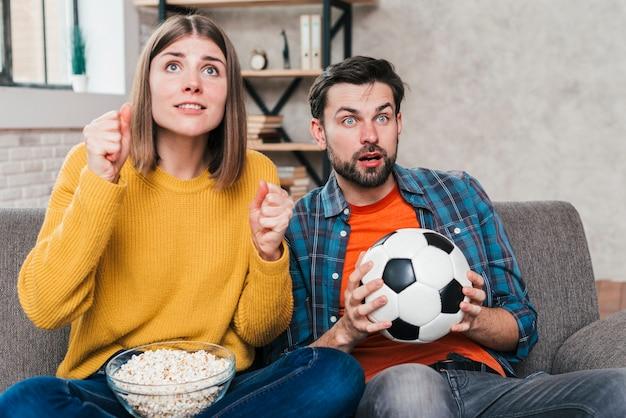 Souriant jeune couple assis sur un canapé en regardant le match de football Photo gratuit