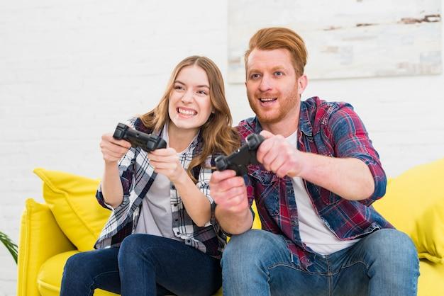 Souriant jeune couple jouant à des jeux informatiques à la maison Photo gratuit