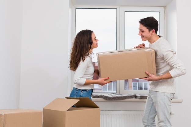 Souriant jeune couple portant une boîte en carton dans le nouvel appartement Photo gratuit