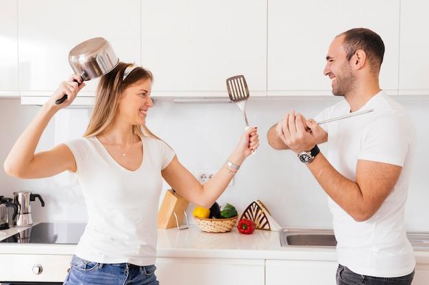 Souriant jeune couple se battre avec un ustensile et une spatule dans la cuisine Photo gratuit