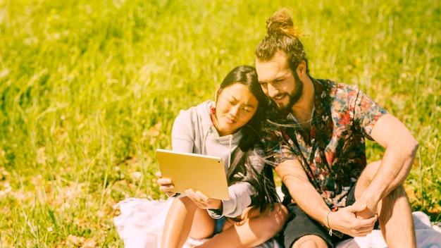 Souriant jeune couple tenant la tablette dans le champ Photo gratuit