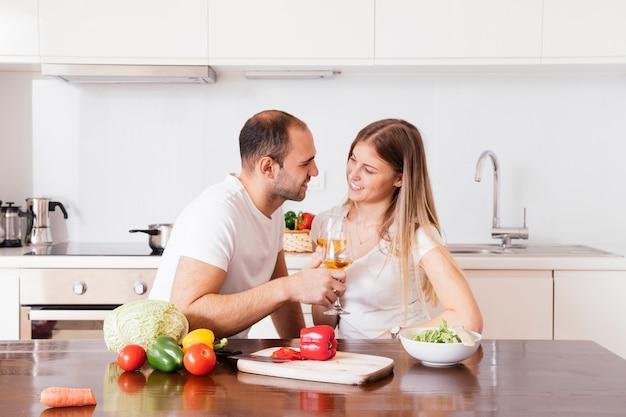 Souriant jeune couple tenant des verres de vin en regardant les uns les autres Photo gratuit