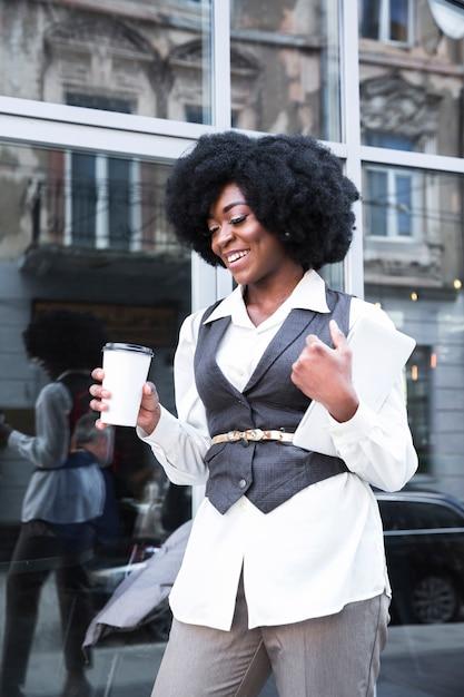 Souriant jeune femme d'affaires africaine tenant la tasse de café à emporter et tablette numérique à la main Photo gratuit