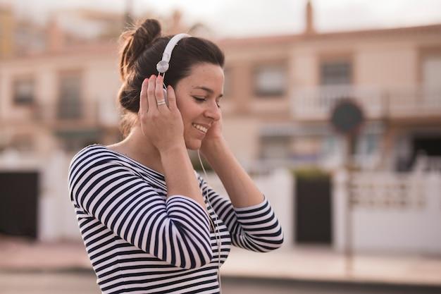 Souriant jeune femme écoutant de la musique sur le casque Photo gratuit