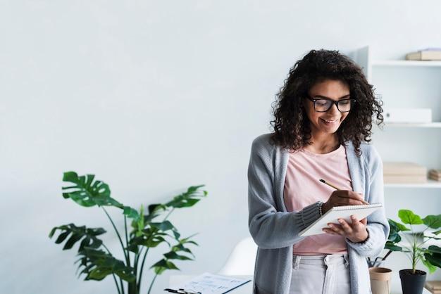 Souriant jeune femme écrit dans le bloc-notes en milieu de travail Photo gratuit