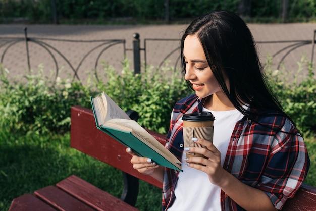 Souriant jeune femme lisant un livre avec une tasse de café jetable, assis sur un banc dans un parc Photo gratuit