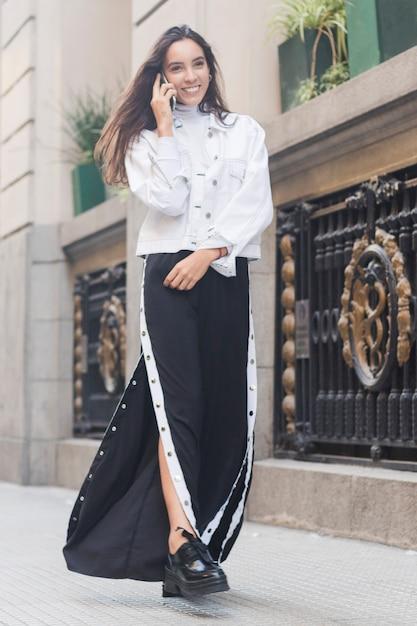 Souriant jeune femme mannequin marchant sur le trottoir parlant au téléphone mobile Photo gratuit