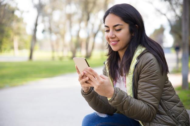 Souriant jeune femme sms sms sur smartphone Photo gratuit