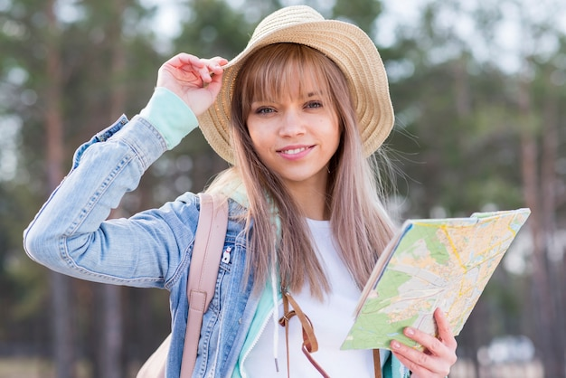 Souriant jeune femme voyageur portant chapeau tenant la carte en main Photo gratuit
