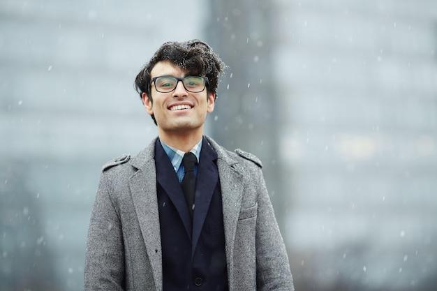 Souriant jeune homme d'affaires dans la neige Photo gratuit