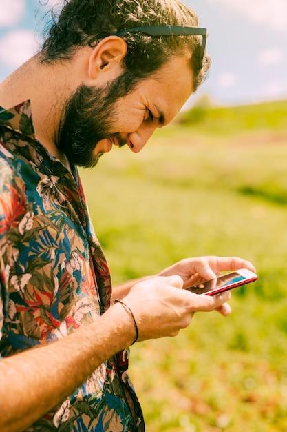 Souriant jeune homme à l'aide de téléphone portable en milieu rural Photo gratuit