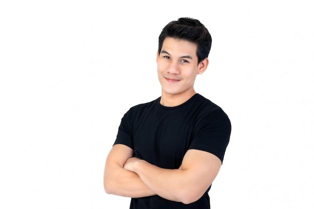 Souriant jeune homme asiatique en t-shirt noir occasionnel avec les bras croisés Photo Premium