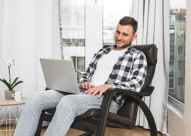 Souriant jeune homme assis sur une chaise à l'aide de téléphone portable à la maison Photo gratuit