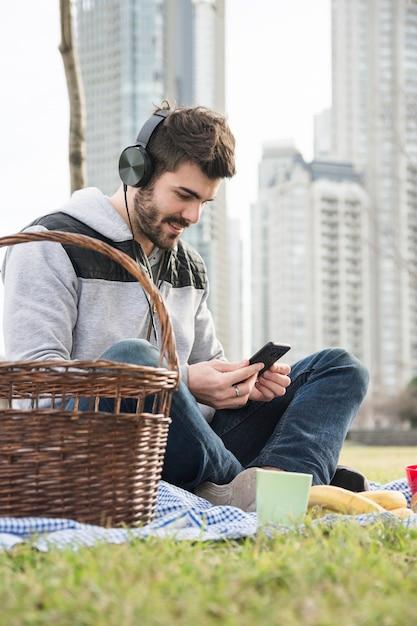 Souriant jeune homme assis dans le parc en écoutant de la musique sur téléphone portable Photo gratuit
