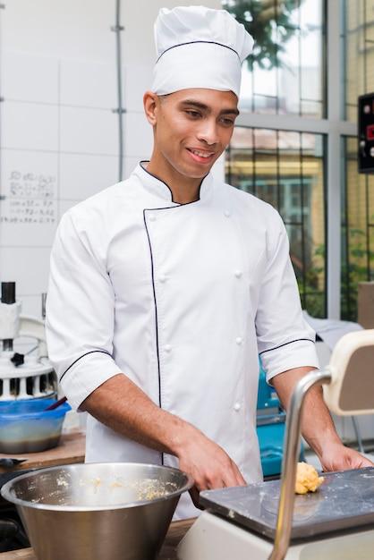 Souriant jeune homme boulanger pesant la pâte à pétrir sur la balance dans la cuisine commerciale Photo gratuit
