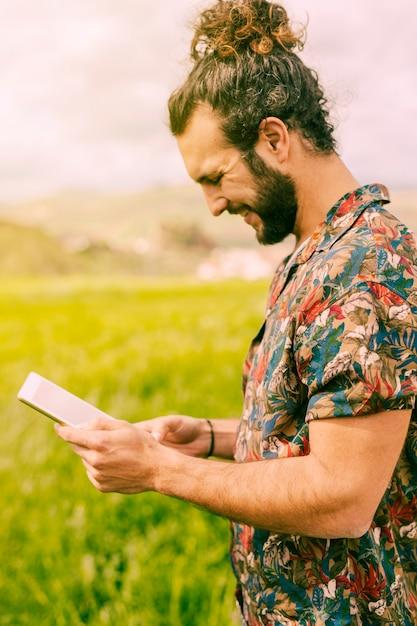 Souriant jeune homme brune debout avec tablette dans le champ Photo gratuit