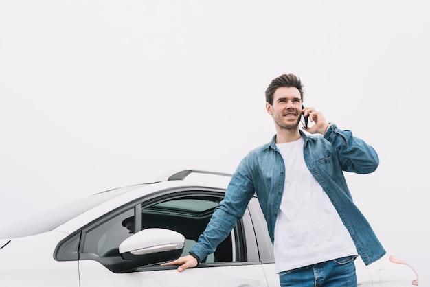 Souriant jeune homme debout devant la voiture parle sur smartphone Photo gratuit