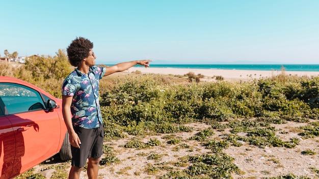 Souriant jeune homme ethnique debout au bord de la mer et indiquant la direction Photo gratuit