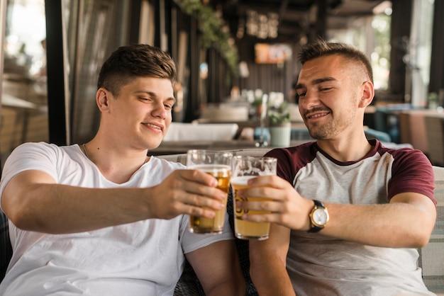 Souriant jeune homme grillage des verres à bière dans le restaurant Photo gratuit