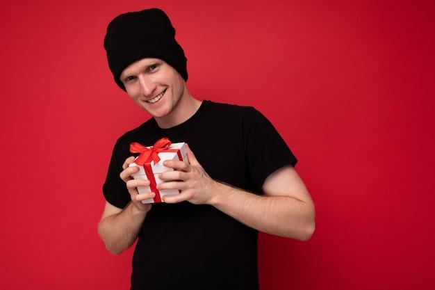 Souriant Jeune Homme Isolé Sur Fond Rouge Mur Portant Un Chapeau Noir Et Un T-shirt Noir Tenant Une Boîte Cadeau Blanche Avec Ruban Rouge Et Regardant La Caméra. Photo Premium