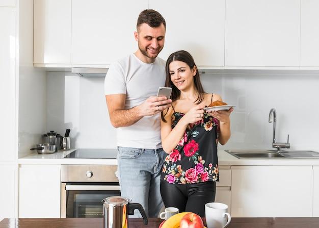 Souriant jeune homme montrant à sa petite amie quelque chose sur son téléphone portable dans la cuisine Photo gratuit