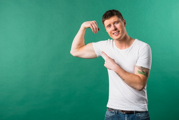 Souriant jeune homme montrant son muscle musculaire sur fond vert Photo gratuit