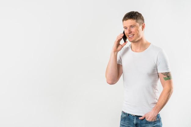 Souriant jeune homme parle au téléphone portable avec sa main dans la poche Photo gratuit