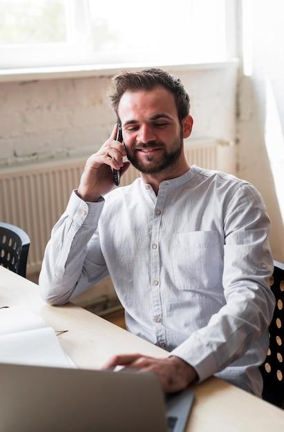 Souriant jeune homme parle sur téléphone portable au lieu de travail Photo gratuit