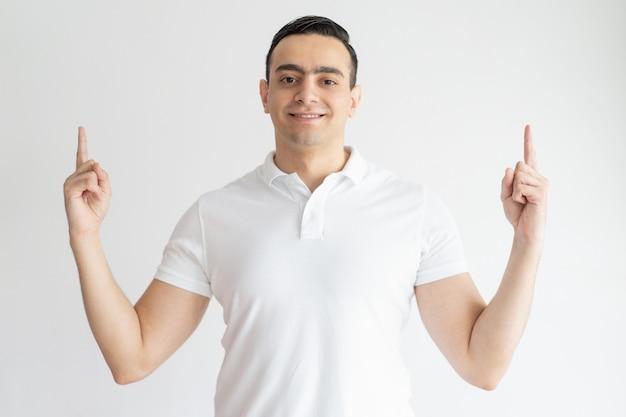 Souriant Jeune Homme Pointant Vers Le Haut Et Regardant La Caméra Photo gratuit