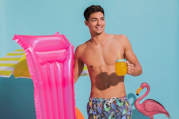 Souriant jeune homme posant avec boisson et matelas de piscine en studio Photo gratuit