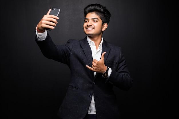 Souriant Jeune Homme Prenant Une Photo De Selfie Sur Smartphone. Guy Indien à L'aide D'un Appareil Numérique. Concept De Photo Selfie. Vue De Face Isolée Sur Mur Noir. Photo gratuit