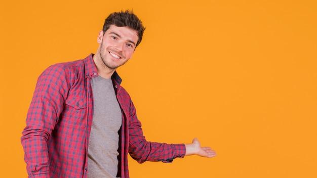 Souriant jeune homme présentant quelque chose sur un fond orange Photo gratuit