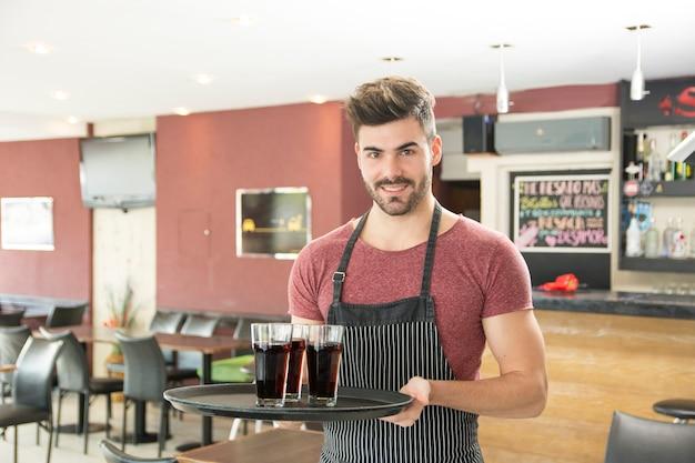 Souriant jeune homme servant des verres de boissons dans le restaurant Photo gratuit