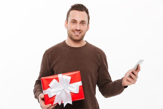 Souriant Jeune Homme Tenant Une Boîte Cadeau Surprise. Photo gratuit