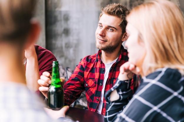 Souriant jeune homme tenant la bouteille de bière à la main, assis avec son ami Photo gratuit