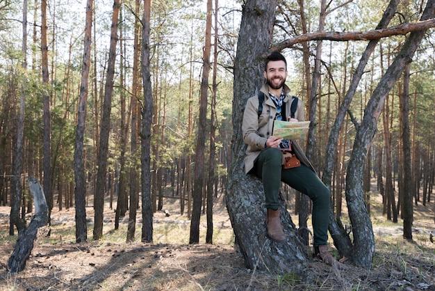 Souriant jeune homme tenant la carte dans la main, assis sous l'arbre dans la forêt Photo gratuit