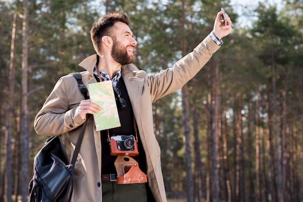 Souriant jeune homme tenant la carte dans la main prenant selfie dans la forêt avec téléphone portable Photo gratuit