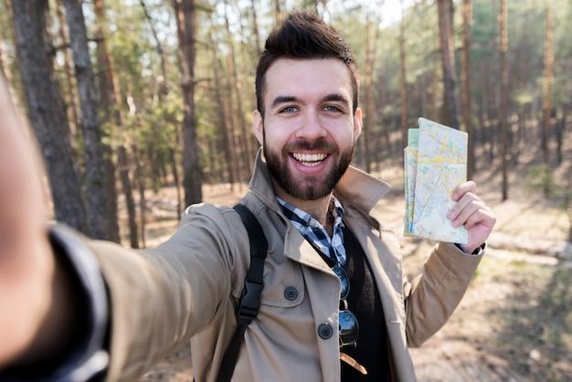 Souriant jeune homme tenant la carte dans la main prenant selfie dans la forêt Photo gratuit