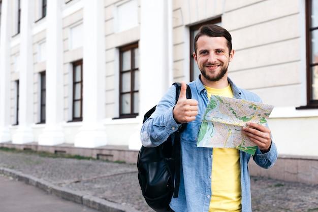 Souriant jeune homme tenant la carte et montrant le pouce vers le haut de geste à l'extérieur Photo gratuit