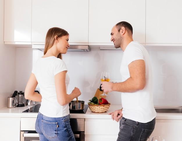 Souriant jeune homme tenant un verre à vin dans la main en regardant sa femme préparer un repas dans la cuisine Photo gratuit